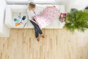 mujer en el sofá mirando muestra de papel tapiz foto