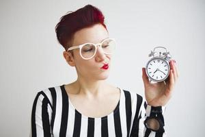 red-haired woman holding alarm clock looking upset photo