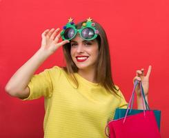 Woman with Christmas party glasses and shopping bags