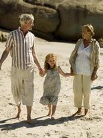 girl walking on the beach with her grandparents.