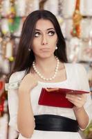 Linda mujer quebrada en compras comprobando cartera
