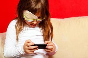 Niña con gafas jugando juegos en el teléfono inteligente en casa foto