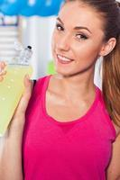 Young girl drinking isotonic drink, gym. Positive emotions. photo
