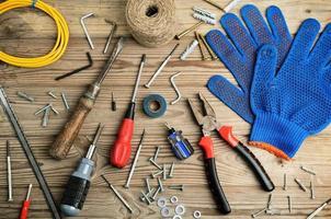 luvas e conjunto de ferramentas em uma mesa de madeira horizontal