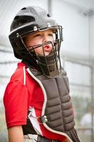 Child baseball player wearing catcher gear