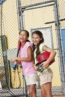 Girls laughing in batting cage photo