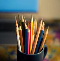 Stack of pencils in a glass on wooden background.