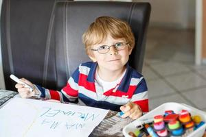 Kid boy in glasses making school homework at home photo