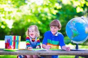crianças fazendo lição de casa no pátio da escola