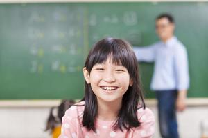 close-up pupils smiling in class with teacher