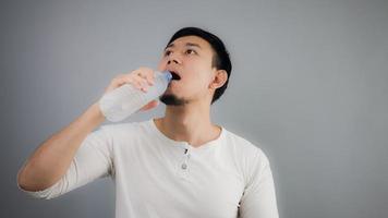 An Asian man drinking water. photo