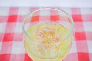 bebida de agua amarilla sobre vidrio foto