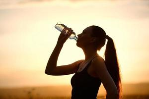Woman silhouette drinking water