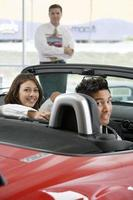 Couple sitting in red convertible in car showroom, salesman