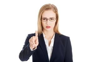 Confused business woman in eyeglasses is looking at her finger.