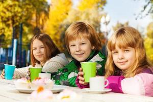 niños felices con tazas de té sentado afuera foto