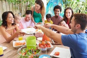 Grupo de familias disfrutando de comida al aire libre en casa