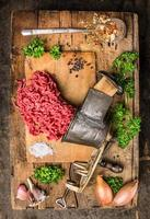 Mincemeat of vintage meat grinder on wooden table with herbs