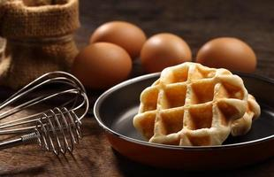 Close up waffles inside teflon pan with whisk and eggs photo