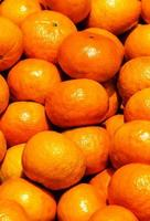 Bunch of fresh tangerines oranges on market.