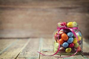 Candy jar decorated with a bow against rustic wooden background