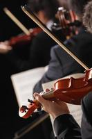 Close-up from behind of a violinist in a symphony orchestra