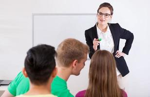 Young teacher pointing on talking student photo