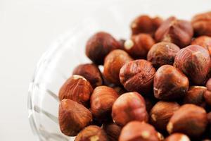 Bowl of hazelnuts on a white background