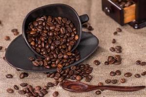 granos de café en una taza de café sobre tela de saco