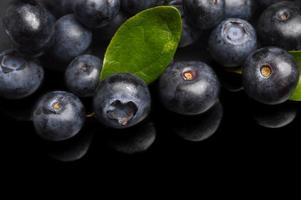 Several whole blueberries with leaves isolated on black corner