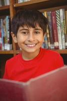 Cute boy reading book in library