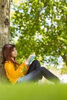 Female college reading book against tree trunk in park