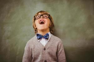 Boy laughing in front of blackboard photo