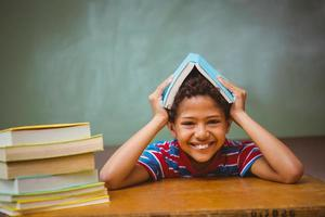 Little boy holding book over head in classroom photo