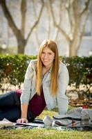 Chica joven estudiante en el campus del parque con libros estudiando feliz