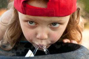 child drinking from water fountain photo
