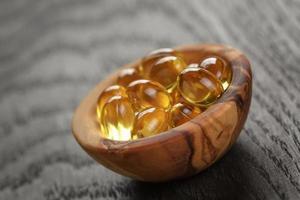 cápsulas de aceite de pescado en un tazón de madera en la mesa de madera