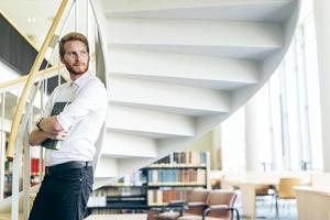Handsome intelligent guy reading a book in a library photo