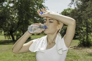 atractiva mujer rubia agua potable
