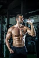 Man drinking water in gym photo