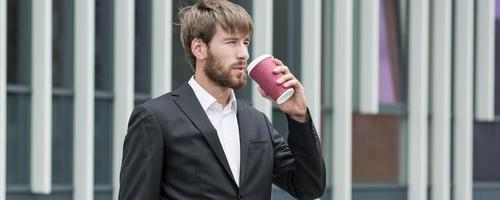Handsome young boss drinking coffee