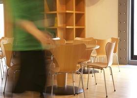 mujer caminando cerca de mesas y sillas foto