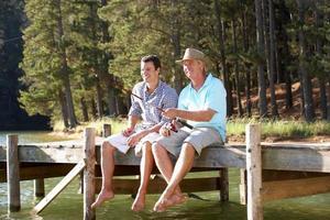 lachende vader en volwassen zoon zittend op een dok, vissen