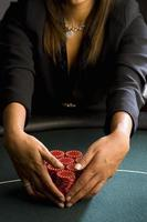 Woman collecting piles of gambling chips on table, mid section photo
