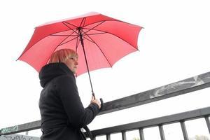 Mujer joven con pie de paraguas rojo en la baranda, Berlín