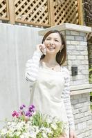 Woman talking on mobile phone in front of house photo