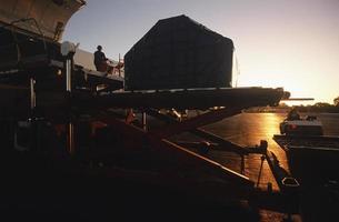 Ground crew servicing airplane at sunset photo