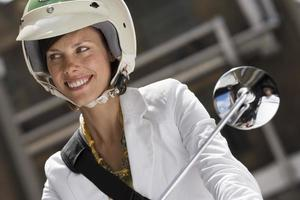 Woman in crash helmet riding on scooter in street, close-up