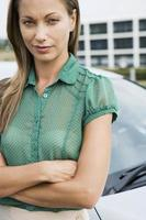 Woman in green short-sleeved blouse standing beside car, arms fo