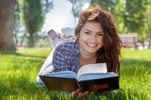 Girl with book in the summer park photo